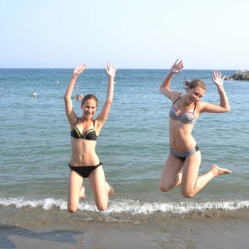 Students jumping in a sandy beach in cyprus